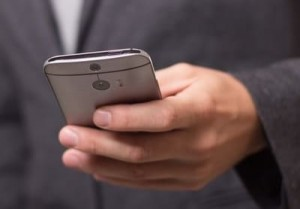 Мужчина держит смартфон в руке